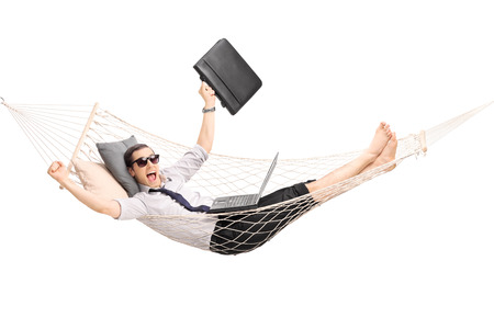 Young businessman lying in a hammock with a laptop in his lap and gesturing joy isolated on white background
