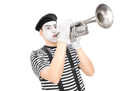 mimo: Studio foto de una joven mimo masculina que toca una trompeta aislado en fondo blanco