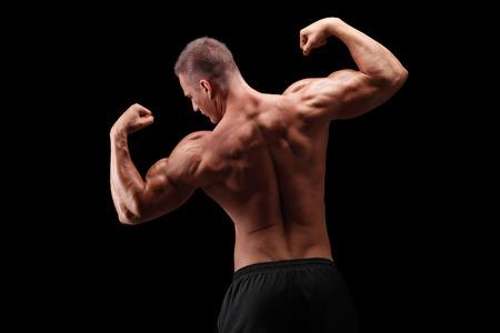 muscle: Vista posterior disparo de un culturista guapo flexionando sus hombros y músculos de la espalda sobre fondo negro Foto de archivo