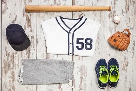 Bunch of sportswear and baseball equipment on a white hardwood floor photo