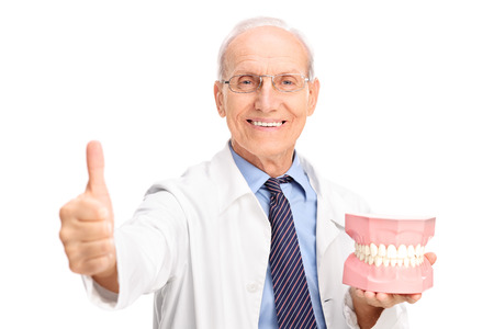 denture: Mature dentist holding a big denture and giving a thumb up isolated on white background