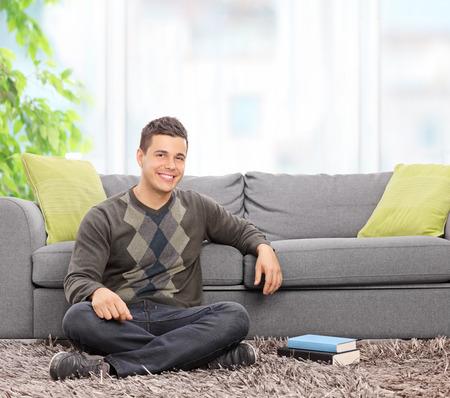 hombre sentado: Joven relajante sentado en casa delante de un sofá gris con par de libros al lado de él tomadas con lente de inclinación y giro Foto de archivo