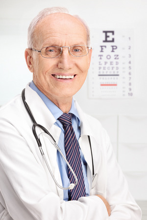 Close up on a mature optician posing in his office with an eyesight test in the background photo