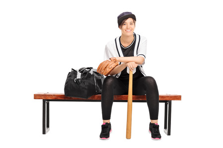 player bench: Female baseball player sitting on a bench and looking at the camera isolated on white background Stock Photo
