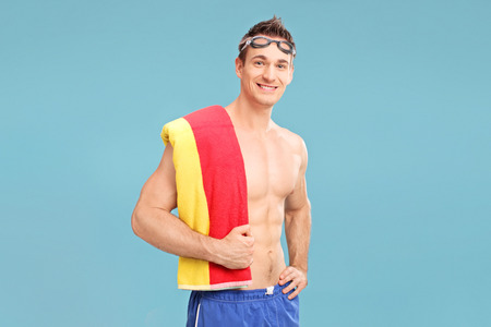 shoulder carrying: Handsome young man with swimming goggles carrying a towel over his shoulder on blue background Stock Photo