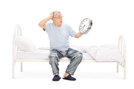 late sixties: Shocked senior man in pajamas sitting on a bed and holding a big wall clock isolated on white background
