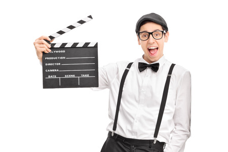 movie director: Young movie director holding a movie clapperboard and leaning against a wall isolated on white background Stock Photo