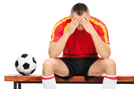 player bench: Worried young football player sitting on a wooden bench isolated on white background