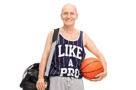 Senior man in sportswear holding a basketball and looking at the camera isolated on white background photo