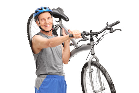 shoulder carrying: Active senior biker carrying his bicycle over his shoulder and looking at the camera isolated on white background Stock Photo