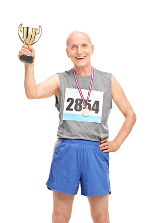 Vertical shot of a joyful mature runner holding a trophy and celebrating his victory isolated on white background photo