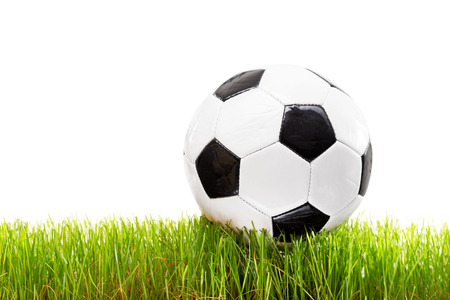 football match lawns: White and black football on a grass surface isolated on white background Stock Photo
