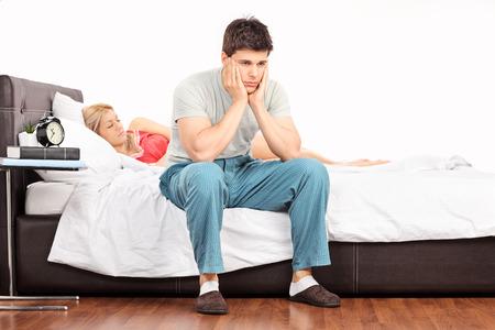 mirada triste: Hombre joven preocupante que se sienta en una cama y contemplando con su novia durmiendo en el fondo