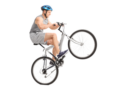 wheelie: Studio shot of a joyful young biker doing a wheelie with his bicycle isolated on white background