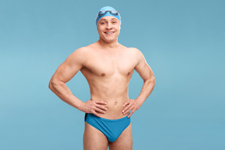 swimming cap: Young male swimmer with swimming cap and goggles posing shirtless on blue background