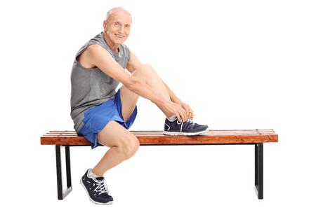 personas sentadas: Studio foto de una mayor alegre en ropa deportiva atarse los cordones de los zapatos sentados en un banco y mirando a la c�mara aislada en el fondo blanco