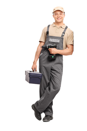 hand drill: Full length portrait of a young worker in gray uniform holding a toolbox and a hand drill and leaning against a wall isolated on white background