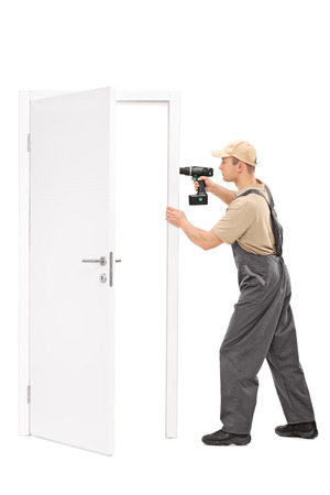hand drill: Full length portrait of a young manual worker installing a door with a hand drill isolated on white background