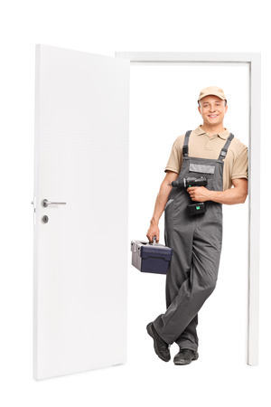 hand drill: Full length portrait of a young male worker holding a toolbox and a hand drill and leaning against the frame of an open door isolated on white background
