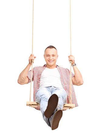 swing: Vertical shot of a carefree young man swinging on a wooden swing and looking at the camera isolated on white background