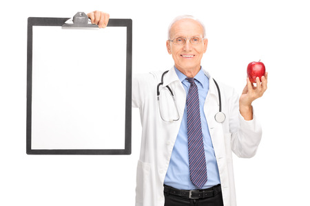 it is isolated: Mature doctor holding a red apple and a clipboard with a blank white paper on it isolated on white background