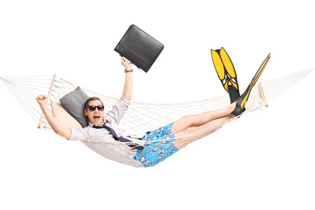 Happy businessman lying in a hammock and gesturing joy with his hands isolated on white background Stock Photo