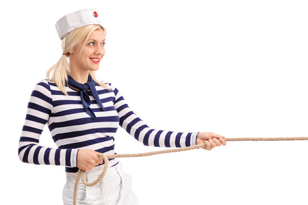 tug: Cheerful female sailor pulling a rope and smiling isolated on white background
