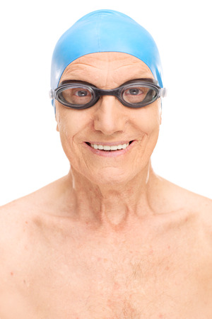 persona de la tercera edad: Primer plano de un hombre mayor con un azul gorro de baño y gafas de natación negro aislado en fondo blanco