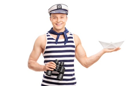 sailors: Cheerful young sailor holding binoculars and a paper boat isolated on white background