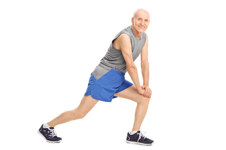 doing: Active senior man doing stretching exercises and looking at the camera isolated on white background
