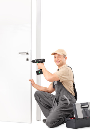 locksmith: Vertical shot of a young locksmith screwing a lock on a door with a hand drill and looking at the camera isolated on white background Stock Photo