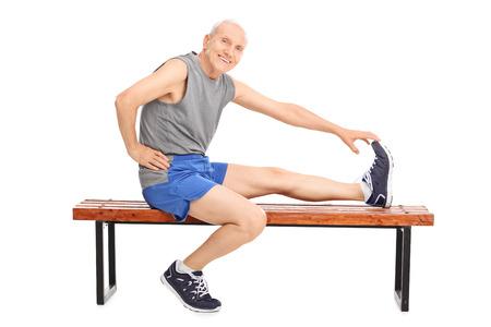 estiramientos: Senior en ropa deportiva sentado en un banco de madera y estira su pierna aislado en fondo blanco Foto de archivo