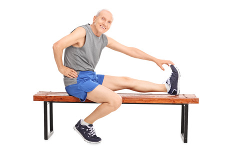 old man happy: Senior in sportswear sitting on a wooden bench and stretching his leg isolated on white background