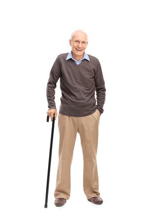 Volledige lengte portret van een senior man met een stok glimlachen en poseren geïsoleerd op witte achtergrond