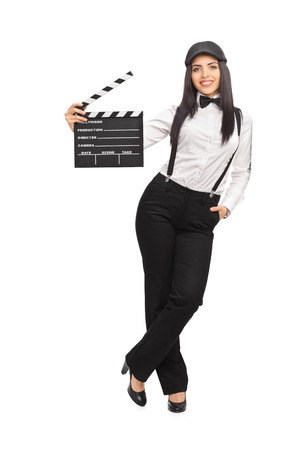 movie director: Full length portrait of a female movie director in an artistic outfit and holding a clapperboard isolated on white background