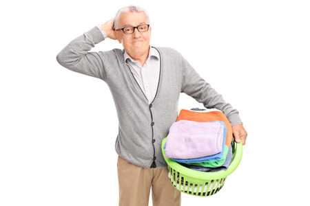 man laundry: Confused senior holding a laundry basket full of clothes and looking at the camera isolated on white background