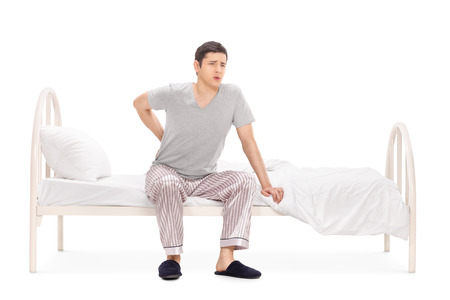 displacement: Young man having a back pain seated on a bed in his pajamas isolated on white background