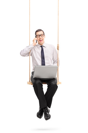 phone isolated: Vertical shot of a young businessman speaking on his cell phone seated on a swing isolated on white background Stock Photo