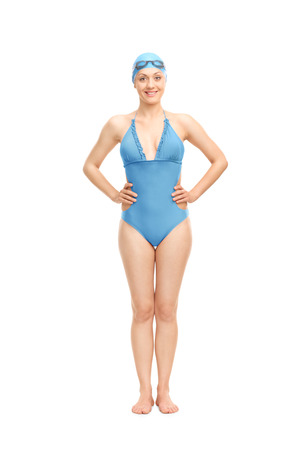 swimming costume: Full length portrait of a female swimmer in a blue swimming costume and a swim cap smiling and looking at the camera isolated on white background Stock Photo