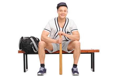 player bench: Young baseball player sitting on a wooden bench and holding a baseball bat isolated on white background