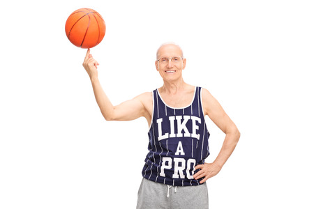 Senior man in a dark blue jersey spinning a basketball on his finger and looking at the camera isolated on white background photo