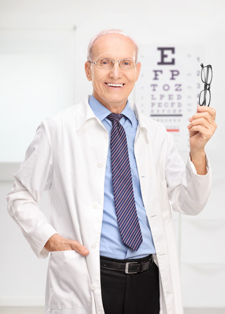 Vertical shot of a mature optician holding a pair of glasses and posing in his office in front of an eye chart photo