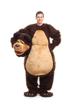 クマの縫いぐるみを笑みを浮かべて、白い背景で隔離のカメラ目線で若い男の完全な長さの肖像画