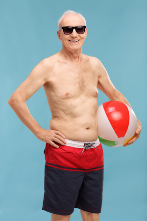swimming shorts: Vertical shot of a shirtless senior in swim shorts holding a beach ball and looking at the camera on blue background