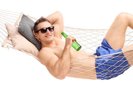 hombre tomando cerveza: Relajado joven acostado en una hamaca y bebiendo una cerveza aisladas sobre fondo blanco