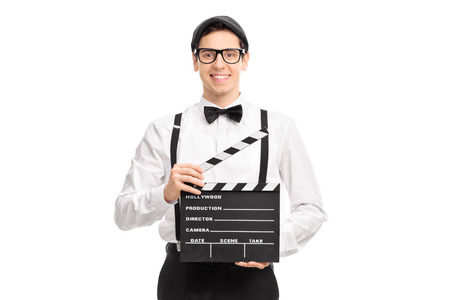 movie director: Young movie director holding a movie clapperboard smiling and looking at the camera isolated on white background