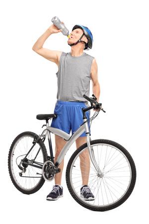 彼の自転車と飲料水は、白い背景で隔離の後ろに立って上級バイカーの完全な長さの肖像画