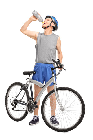 Full length portrait of a senior biker standing behind his bicycle and drinking water isolated on white background