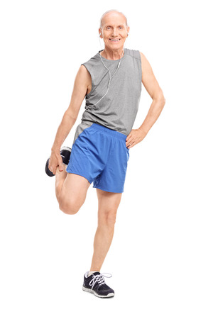Full length portrait of a senior in sportswear stretching his leg and listening music on headphones isolated on white background photo