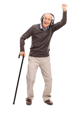 male senior adults: Full length portrait of an overjoyed senior holding a cane and listening to music on headphones isolated on white background Stock Photo